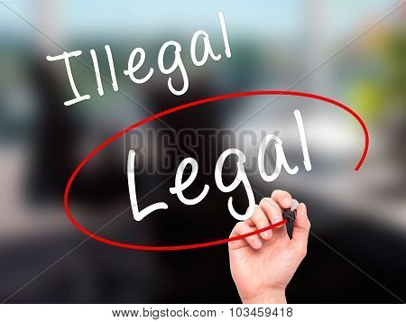 Man Hand writing and Choosing Legal instead of Illegal with black marker on visual screen.