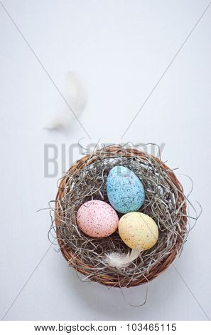 Colorful speckled eggs with feathers in a nest shot overhead for easter celebrations, table decorations