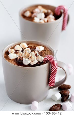 Cup of hot chocolate cocoa drink with toasted marshmallows and a candy cane, christmas dessert sweets
