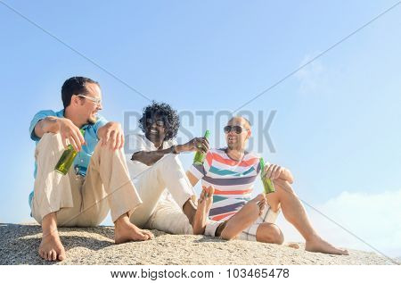 Friends hanging out by the beach drinking beers, enjoying the sunny afternoon, clear blue sky, lots of copy space