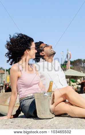 Mix race couple relaxing by the seaside, enjoying each others company on their honeymoon holiday with champagne