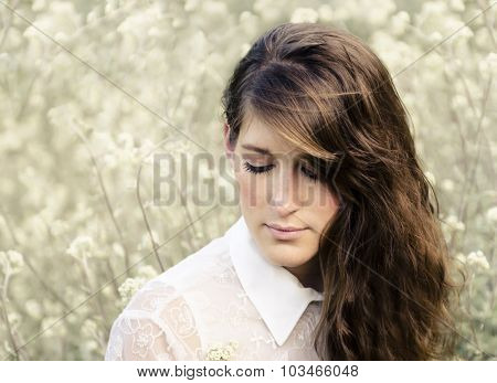 Portrait of a beautiful brunette woman in a field of wild flowers