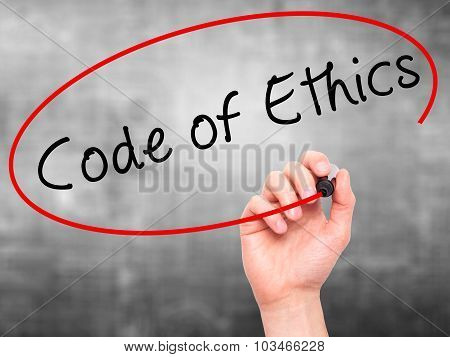 Man Hand writing Code of Ethics with black marker on visual screen.