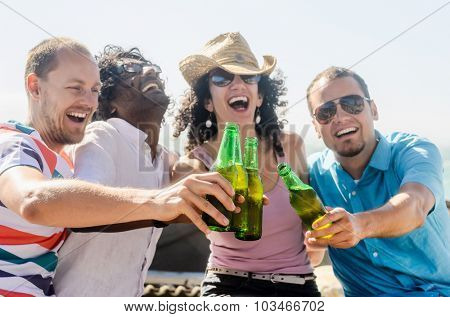 Friends cheers at the beach on a sunny afternoon, a fun party gathering outdoors by the sea