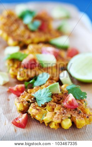 Deep fried corn fritters garnished with  tomato, avocado and coriander