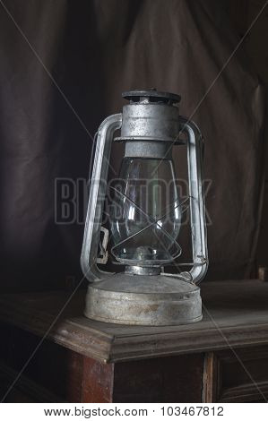 Aging Kerosine Lamp Cost(stand)s On Wooden Table