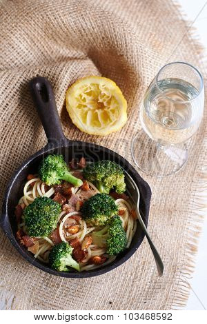Meal in a pan : Broccoli, almonds, bacon, noodles with lemon and glass of water