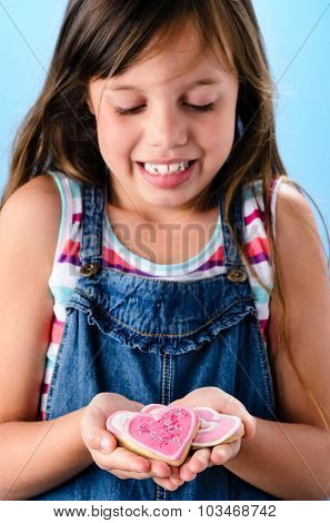 Smiling happy cute young girl in denim dungarees shows her pink heart shape cookies in her hands, valentines or mothers day concept