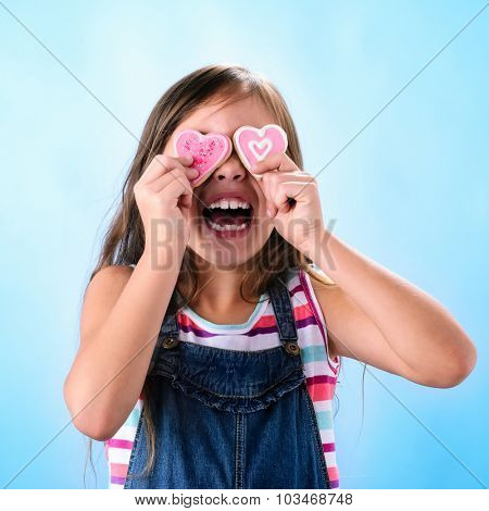 Cute happy young girl in denim dungarees holds pink heart shape cookies over her eyes, on blue background valentines or mothers day concept