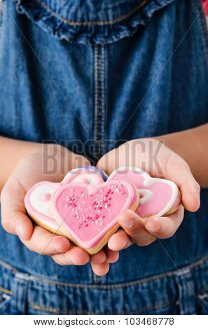 Close up of young girl hands holding several pink heart shape cookies, valentines day concept