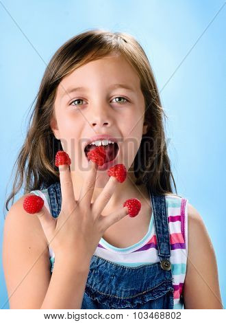 Cute young girl eating and playing with fresh raspberries on her fingertips