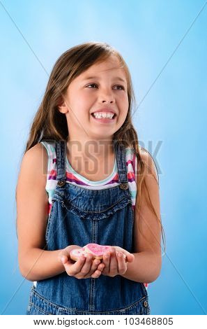 Happy young school girl in denim dungarees holds pink heart shape cookies in her hands, valentines or mothers day concept