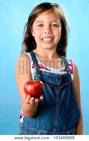 Portrait of adorable girl holding a red apple, isolated on blue part of a healthy diet