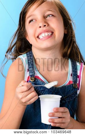 Healthy young girl eating a spoonful of yoghurt, healthy living and eating concept, on blue background