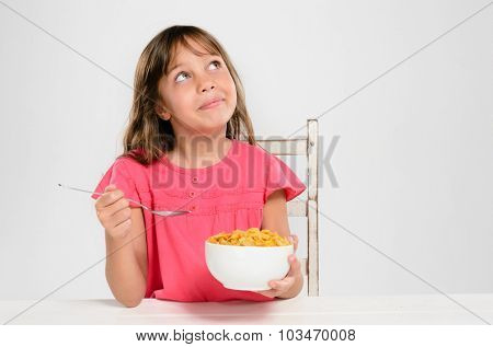 Cute young girl kid holding bowl of breakfast cereal cornflakes looking up, healthy eating and diet concept