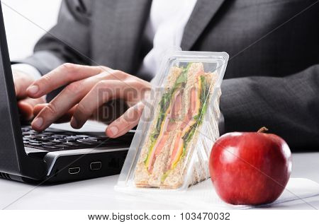 Corporate business worker working on computer, too busy to eat healthy take away lunch sandwich and fresh red apple