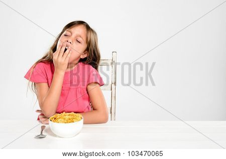 Adorable young girl is sleepy and yawns at the breakfast table with a bowl of nutritious healthy cornflake cereal