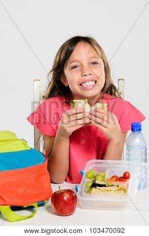 Happy smiling school girl eating her healthy lunch box sandwich with backpack and apple on the table