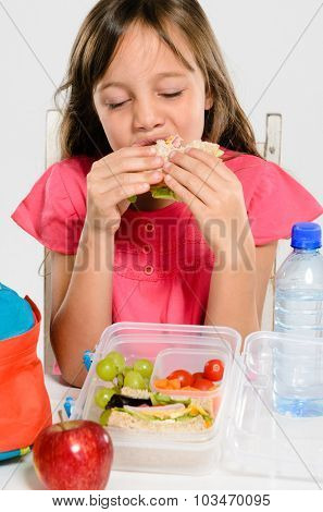 Young elementary school girl eating enjoying her healthy sandwich from her lunch box filled with nutritious food
