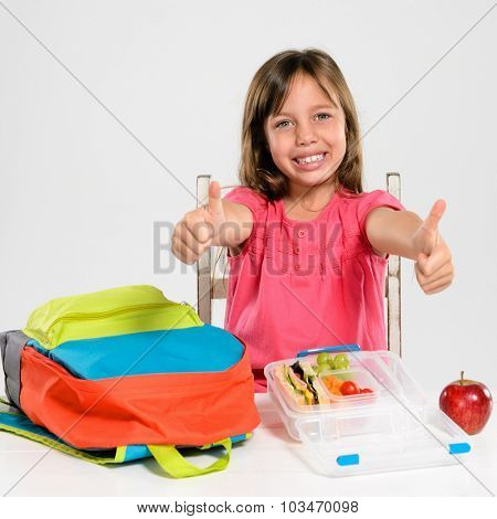 Cute school girl gives the thumbs up for school and a healthy lunch box