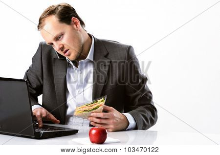 Busy hardworking businessman multi-tasking, talking on mobile cell phone typing on laptop computer and having healthy sandwich lunch with red apple