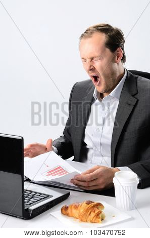 Tired yawning exhausted businessman working tirelessly at his desk, rushing a deadline