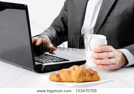 Business man holds coffee while working at desk with breakfast croissant, selective focus on hand