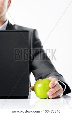Man in business suit behind a laptop holds bright vibrant apple in hand, symbolising new ideas and fresh concepts or healthy lifestyle in the office
