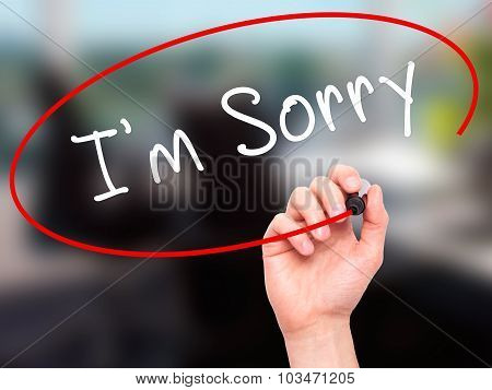 Man Hand writing I'm Sorry with marker on transparent wipe board.