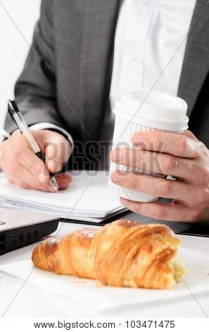 Man in suit writes while having a breakfast croissant and drinks coffee