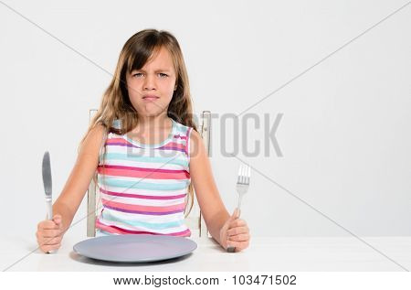 Unhappy kid at table, throwing a tantrum, bad table manners