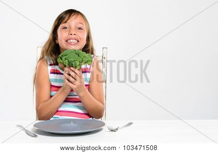 Portrait of happy smiling young girl with her broccoli at the dinner table