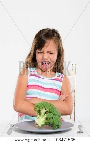 Child looks with disgust at vegetable, refusing to eat it and sticking tongue out