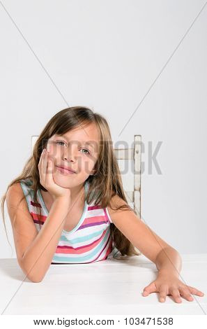 Portrait of cute beautiful adorable young kid sitting at a table smiling