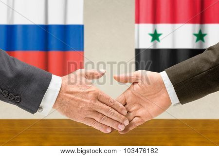 Representatives Of Russia And Syria Shake Hands