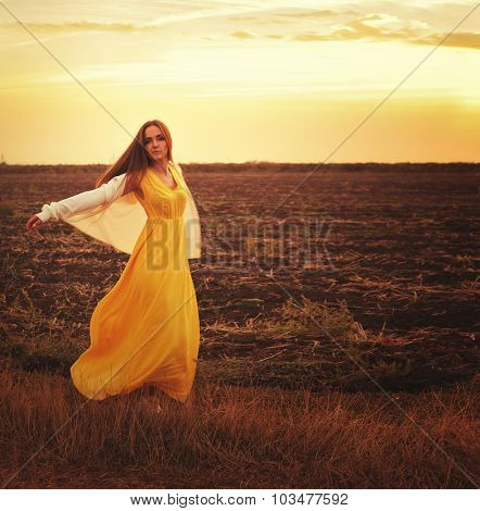 Fashion woman dressed in long yellow dress and white jersey dancing on a sunset autumn field.