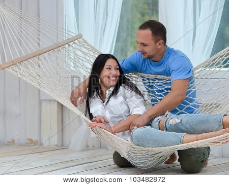 Woman Relaxing In Hammock Smiling And Man Standing