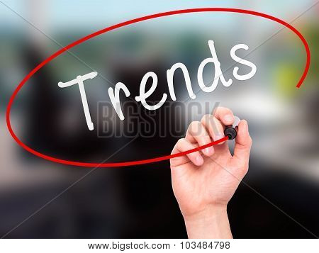 Man Hand writing Trends with marker on transparent wipe board.