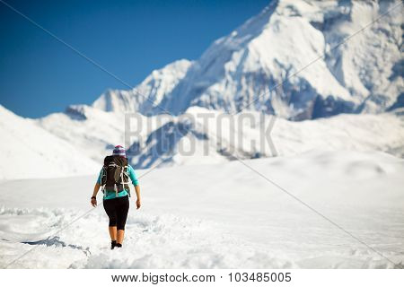 Woman hiker walking in beautiful inspirational winter mountains. Trekking and hiking inspiration and
