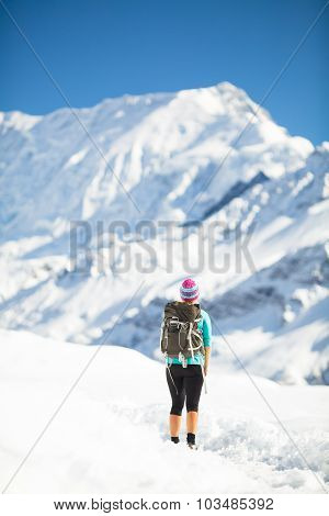 Young happy woman hiker walking in beautiful inspirational winter mountains. Hiking inspiration and