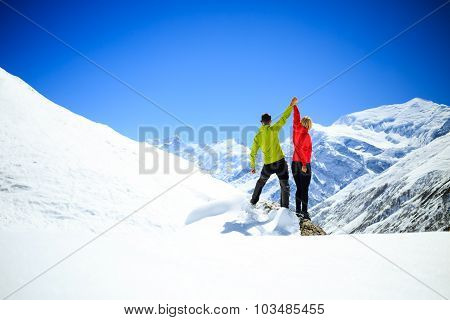 Couple hikers man and woman success in winter mountains. Accomplish and climbing motivation in beaut