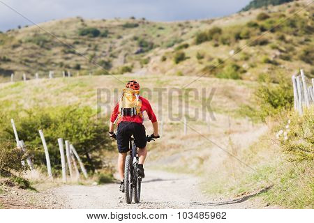 Mountain biker riding enduro on bike in summer mountains landscape. Man MTB adventure cycling with b