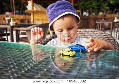 Toddler playing with toy cars. Focus to boy