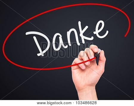 Man Hand writing Danke with marker on transparent wipe board.