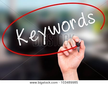 Man Hand writing Keyword with black marker on visual screen.