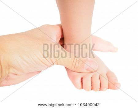 Male Hand Holding Firmly Around A Foot Of Toddler Isolated On White