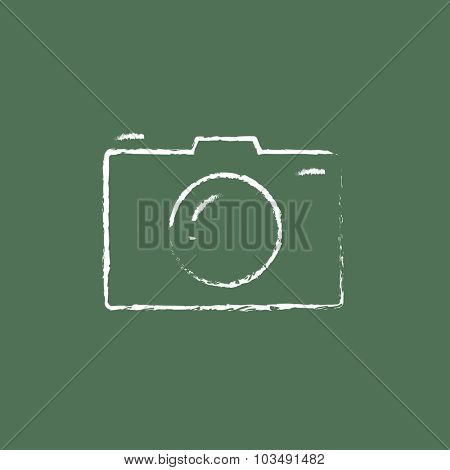 Camera hand drawn in chalk on a blackboard vector white icon isolated on a green background.