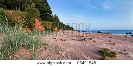 Summer Midnight Landscape On Baltic Sea Shore With Stones, Red Rocks, Sand And Grass.