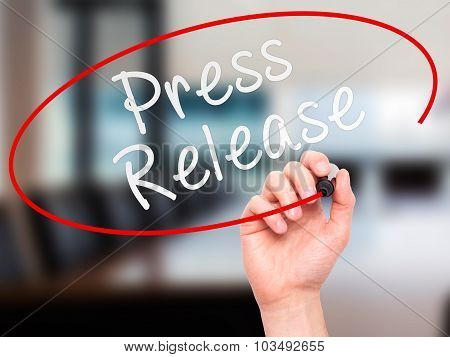 Man Hand writing Press Release with marker on transparent wipe board.
