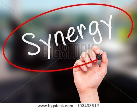 Man Hand writing Synergy black marker on visual screen.